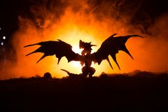 Silhouette of fire breathing dragon with big wings on a dark orange background. Selective focus Stock Image