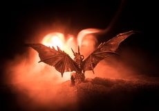 Silhouette of fire breathing dragon with big wings on a dark orange background stock photo
