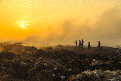 Silhouette Firefighters extinguishing a fire. Wearing smoke mask at landfill garbage large area at sunset Stock Image