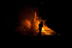 Silhouette of fireman. Fighting a fire at night Stock Photos
