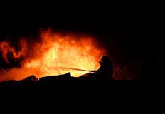 Silhouette of Firemen. Fighting a raging fire with huge flames of burning timber Stock Image