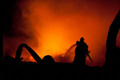Silhouette of Firemen. Fighting a raging fire with huge flames of burning timber Royalty Free Stock Photos