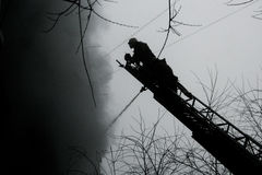 Silhouette of Firemen. Fighting a raging fire with huge flames of burning timber Royalty Free Stock Image