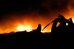 Silhouette of Firemen fighting a raging fire. With huge flames of burning timber Stock Photos