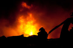 Silhouette of Firemen. Fighting a raging fire with huge flames of burning timber Stock Images