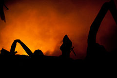 Silhouette of Firemen. Fighting a raging fire with huge flames of burning timber Stock Photo