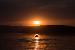 Silhouette of fisher and dog sitting in boat.  Stock Image