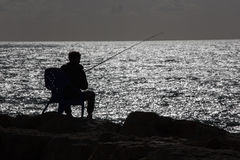 Silhouette of fisher on the seaside in Tel Aviv Stock Images
