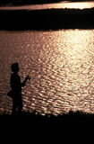 Silhouette of a fisherman. Silhouette of a man fishing at sunset Royalty Free Stock Image