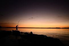 Silhouette of a fisherman. A silhouette of a fisherman that has hooked into a fish Stock Photos