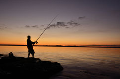 Silhouette of a fisherman. A silhouette of a fisherman on the rocks Stock Photography