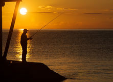 Silhouette of a fisherman Stock Photo