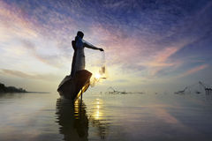 Silhouette Fisherman in action fishing . Silhouette Fisherman catch a fish in action fishing Stock Photo