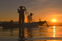 Silhouette Fisherman in action fishing . Silhouette Fisherman catch a fish in action fishing Stock Images