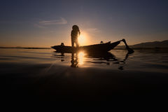 Silhouette Fisherman in action fishing . Silhouette Fisherman catch a fish in action fishing Royalty Free Stock Photography