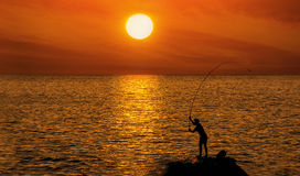 Silhouette of a fisherman on the background of round brilliant setting sun standing on a rock on the sea coast among Royalty Free Stock Image