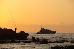 Silhouette of a fisherman on a background of sea sunset Stock Image