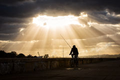Silhouette of fisherman on the bike with rays in the background.  Stock Photo
