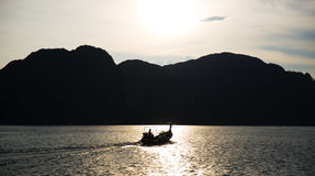 Silhouette of a fisherman and a boat Stock Photography