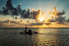Silhouette of fisherman on boat at a beautiful sunrise with colo Royalty Free Stock Images