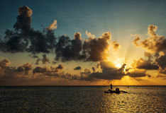 Silhouette of fisherman on boat at a beautiful sunrise with colo Stock Photo