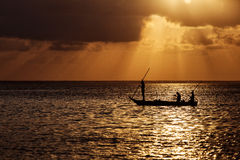 Silhouette of fisherman on boat at a beautiful sunrise with colo Stock Photography