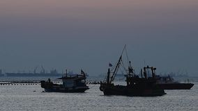 Silhouette of fisherman boat floating stock footage