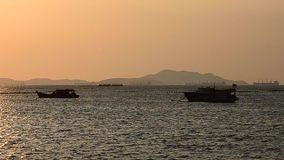Silhouette of fisherman boat floating stock video