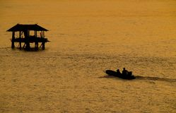 Silhouette of fisherman boat heading towards fisherman`s cottage in river. On golden sunshine at morning time stock photo