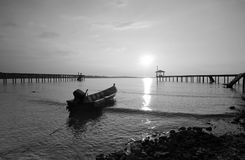 Silhouette of fisherman boat left alone in black and white mode. Stock Photos
