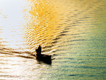Silhouette of fisherman on a boat passing through the sunrise Stock Photos