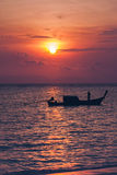 Silhouette of fisherman on boat in the sea with sunrise over hor. Izon behind,Thailand Stock Photo