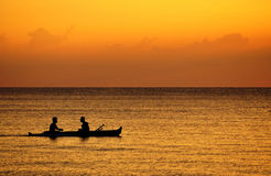 Silhouette of fisherman on a boat. Two Fishermen boating at sunset stock photo