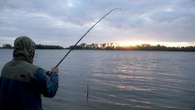 Silhouette fisherman catching fish and spinning fishing reel during biting
