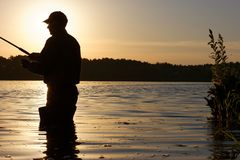 Fisherman. Silhouette of fisherman catching the fish during sunrise Royalty Free Stock Photography