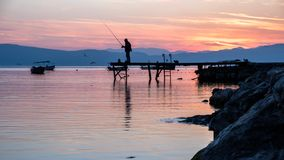 Silhouette of a a fisherman on a jetty at Lake Ohrid, Macedonia, during sunset stock image