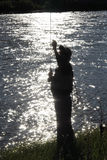 Silhouette of Fisherman at Dusk Checking his line Royalty Free Stock Photo