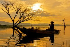 Silhouette fisherman on the fish boat on lake in the sunshine morning. Thailand royalty free stock photo