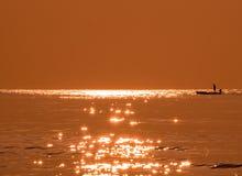 Silhouette fisherman fishing golden sea beautiful shine Stock Photos