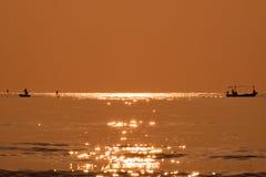 Silhouette fisherman fishing golden sea beautiful shine Stock Image