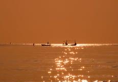 Silhouette fisherman fishing golden sea beautiful shine Stock Photo