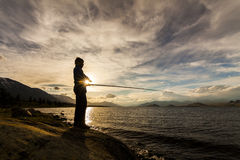 Silhouette of a fisherman with a fishing rod on the background o Royalty Free Stock Photo