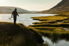 Silhouette of a fisherman with a fishing rod Royalty Free Stock Image