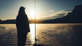 Silhouette fisherman with fishing rod at sunrise sunlight, man enjoy hobby sport on evening lake, outline person catch fish