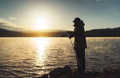 Silhouette fisherman fishing rod at sunrise sunlight, outline man enjoy hobby on evening lake, person catch fish on background
