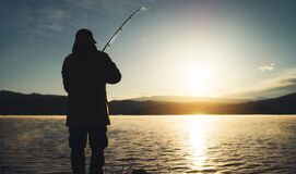 Silhouette fisherman with fishing rod at sunrise sunlight, outline man enjoy hobby sport on evening lake, person catch fish