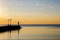 Silhouette of fisherman fishing sea fish at summer dawn Stock Image