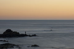 Silhouette of fisherman fishing at sunset Stock Images