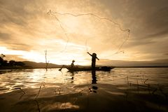 Silhouette Fisherman Fishing by using Net on the boat with sunlight in Thailand, Nature and Culture concept stock image