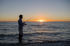 Silhouette of fisherman with hat on the beach with fish rod standing on sea water fishing at sunset with beautiful orange sky in v Royalty Free Stock Image